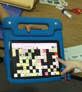 "image of a preschooler holding a Thomas train and touching ""up"" on their iPad with Speak for Yourself, AAC app"