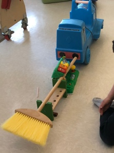 blue Thomas train leading a line of toys that includes a broom... a shoe-less foot is peeking in to the edge of the frame.