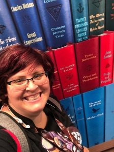 image of white woman with short dark pink hair against a rainbow book backdrop. she has white earbuds slung over her shoulder.