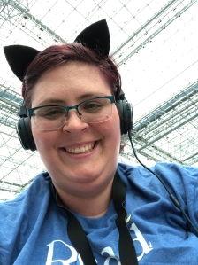 image of smiling white woman with short dark pink hair, wearing cat ears and over the ear headphones