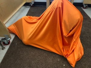 image of a child completely tucked into an orange body sock, no head or arm or leg visible.