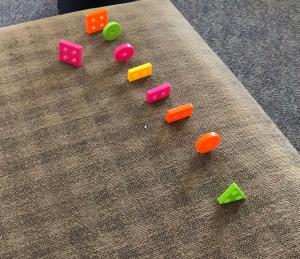 a set of neon shapes in a neat line on a couch cushion