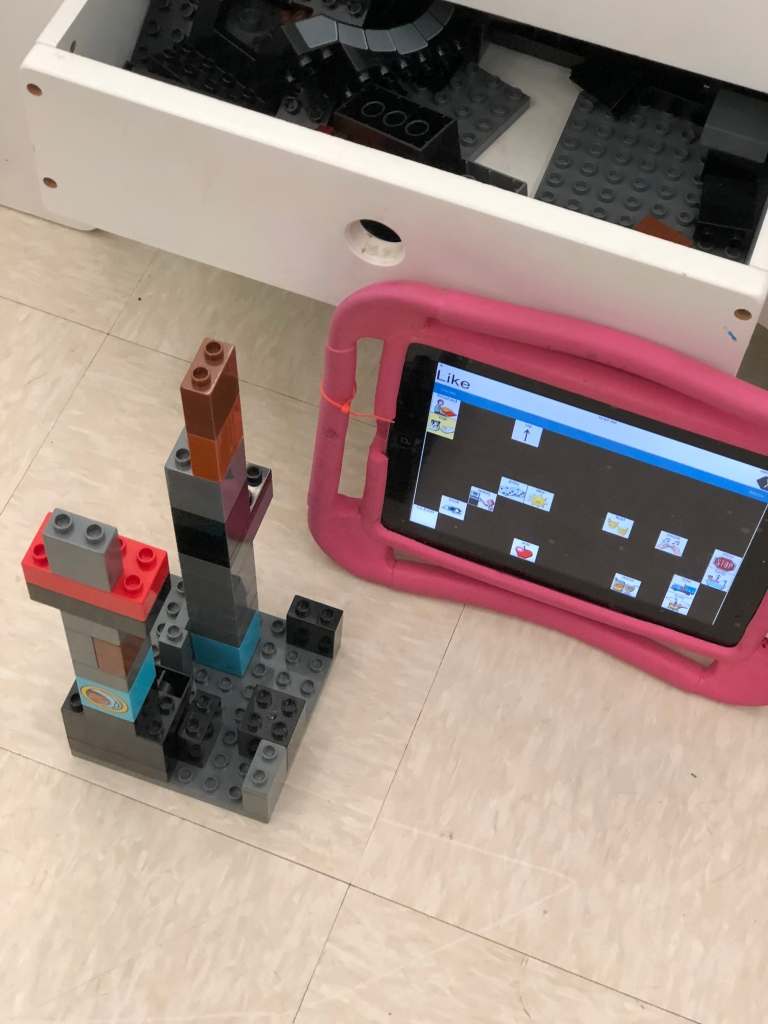 iPad in pink case next to stack of Legos