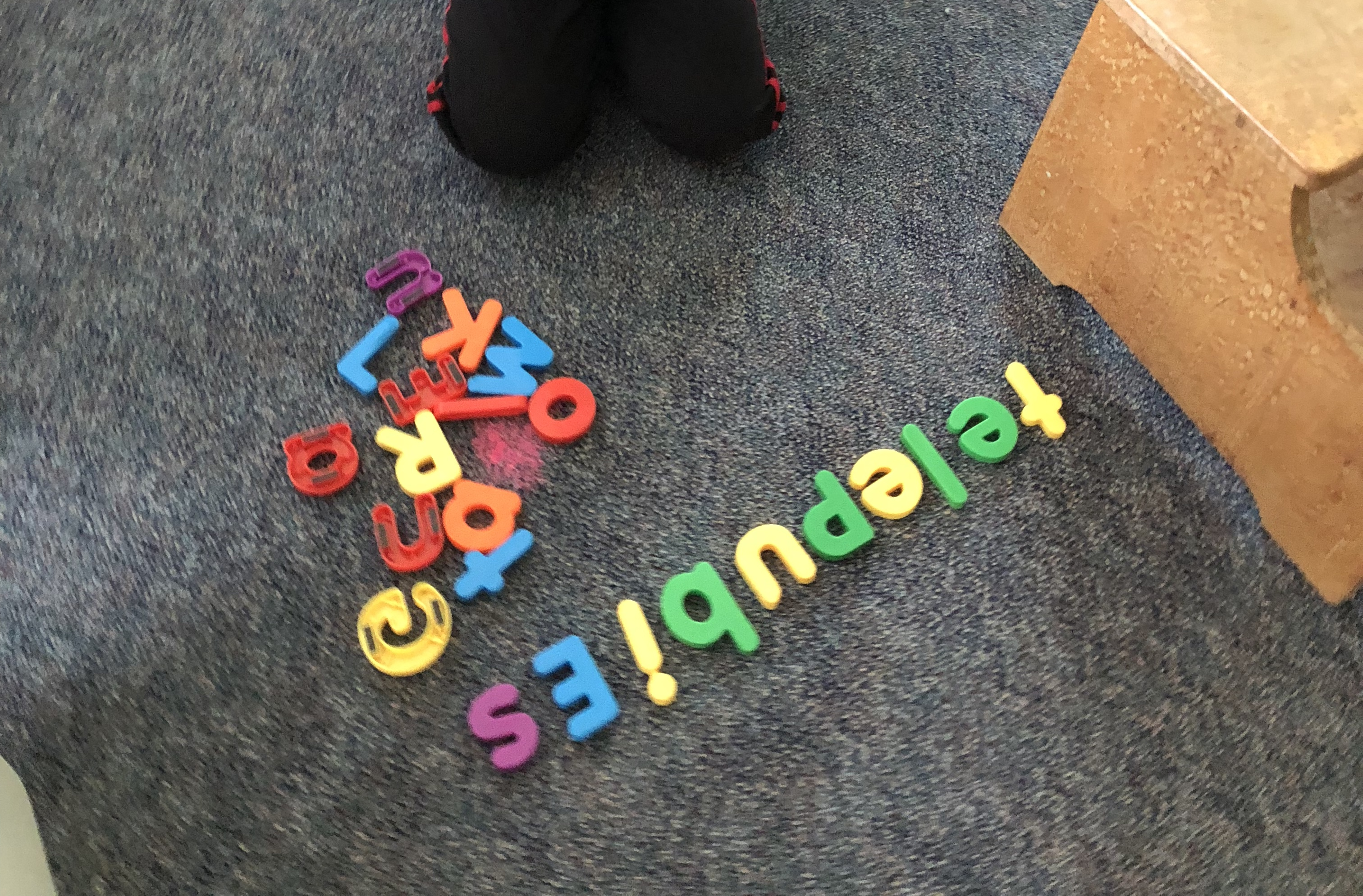 image of rainbow letters on the floor -- telepubies -- an attempt to spell Teletubbies.
