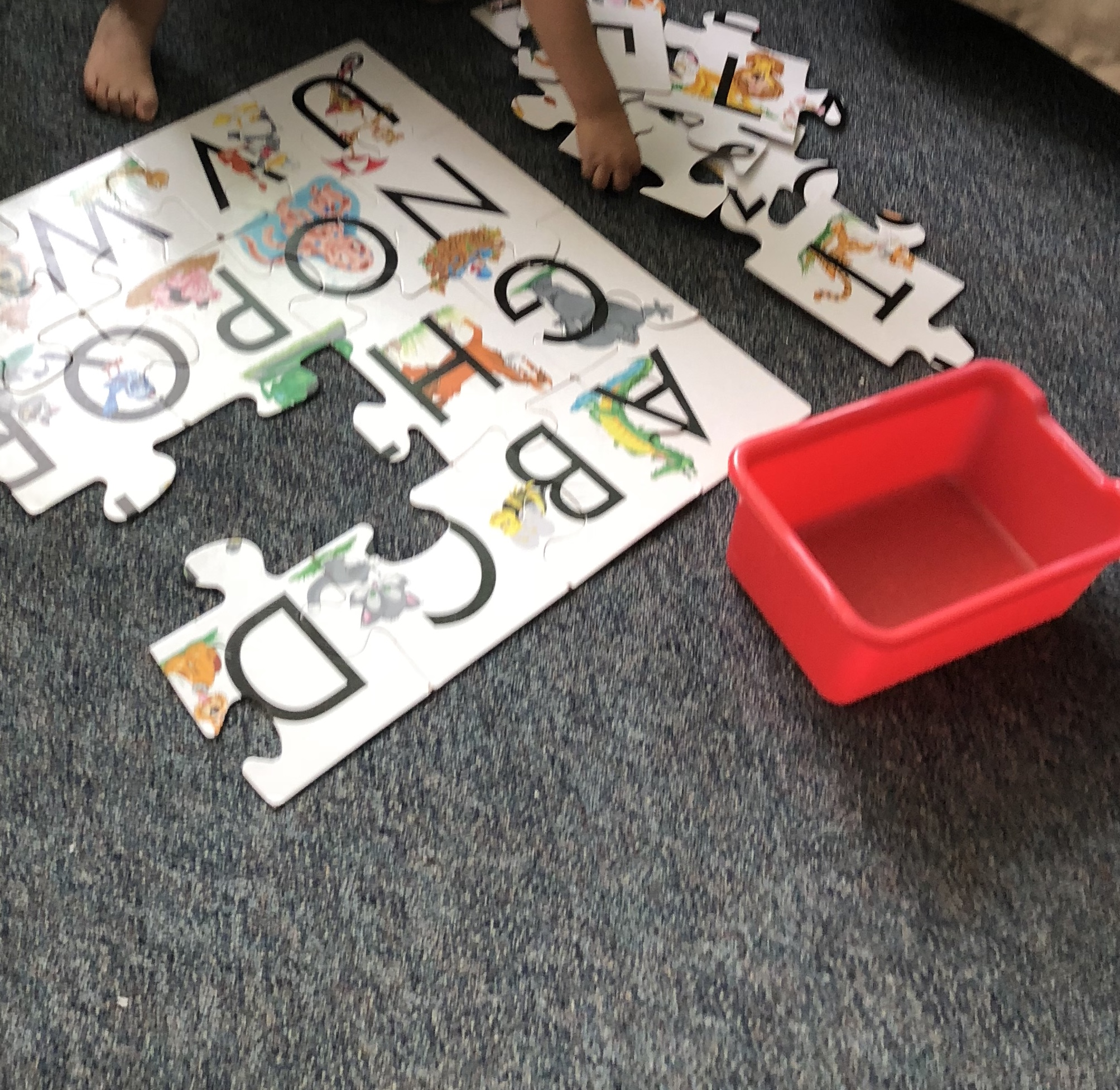 image of an alphabet puzzle on the floor, half completed