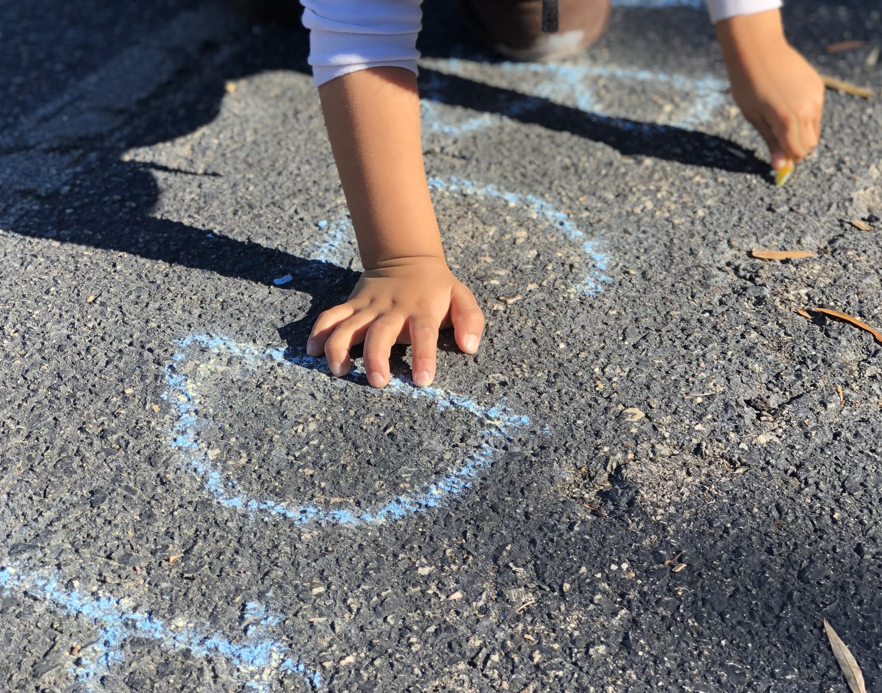 chalk letters on blacktop with a student hand on the D, while they begin tracing with their other hand